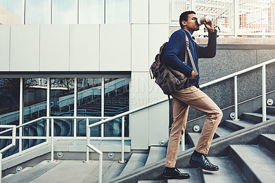 Buy stock photo Shot of a young businessman drinking coffee while walking through the city