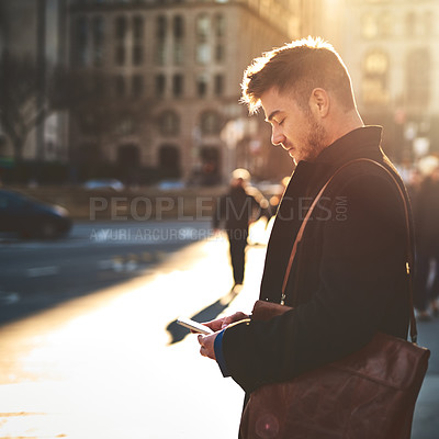 Buy stock photo Shot of a focused young man texting on his phone while standing in the busy streets of the city on his way to work