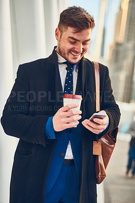 Buy stock photo Shot of a cheerful young man texting on his phone while drinking coffee in the busy streets of the city while going to work in the morning