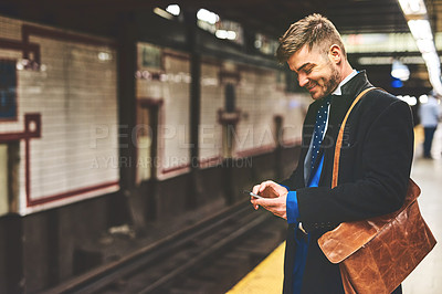 Buy stock photo Shot of a cheerful young man texting on his phone while waiting for a train to take him to work in the morning