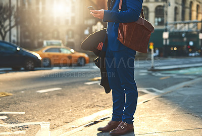 Buy stock photo Low angle shot of a unrecognizable man texting on his phone while waiting for a taxi to take him to work in the morning