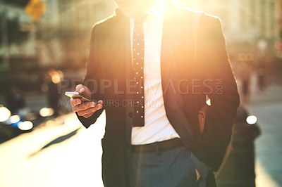 Buy stock photo Shot of an unrecognizable man texting on his cellphone while walking the busy streets of the city in the morning