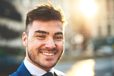Buy stock photo Portrait of a cheerful young businessman standing in the busy streets of the city in the morning