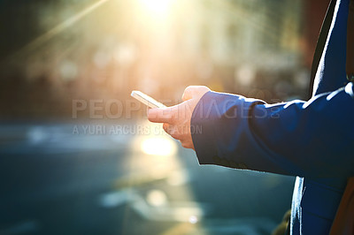 Buy stock photo Shot of an unrecognizable man texting on his phone while waiting for a taxi to get to work in the morning