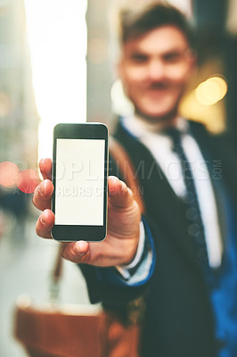 Buy stock photo Closeup of a cheerful young man holding up a cellphone and showing the screen to the camera outside in the city during the day