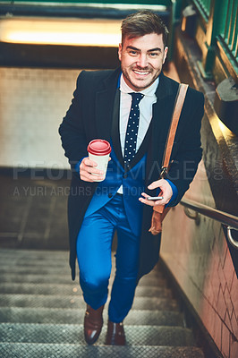 Buy stock photo Portrait of a cheerful young businessman texting on his phone and drinking coffee while walking up a flight of stairs in a subway during the morning hours