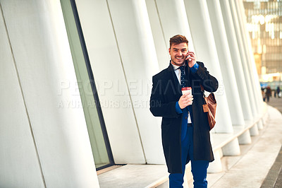 Buy stock photo Portrait of a cheerful young man talking on his phone while drinking coffee at work during the morning hours