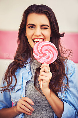 Buy stock photo Portrait of a beautiful young woman holding candy against a wall outside