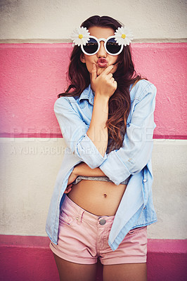 Buy stock photo Cropped shot of a beautiful young woman wearing novelty sunglasses and posing against a wall outside