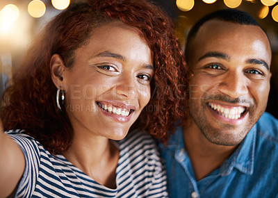 Buy stock photo Cropped shot of an affectionate young couple taking selfies while sitting in a coffee shop
