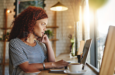 Buy stock photo Shot of an attractive young woman working on a laptop in a cafe