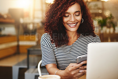 Buy stock photo Shot of an attractive young woman using a cellphone and laptop in a cafe