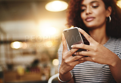 Buy stock photo Closeup shot of a young woman using a cellphone in a cafe