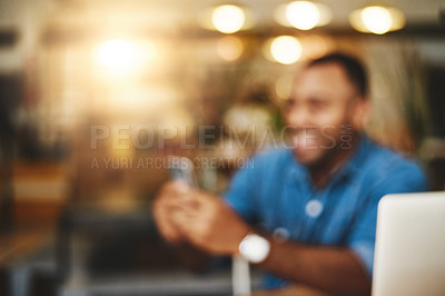 Buy stock photo Defocused shot of a young man using a cellphone in a cafe