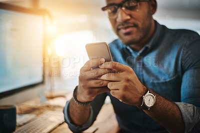 Buy stock photo Cropped shot of a young businessman using a mobile phone during a late night at work