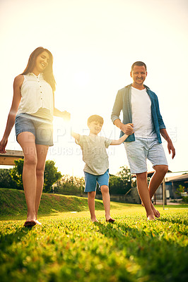Buy stock photo Shot of a young family spending the day in the backyard