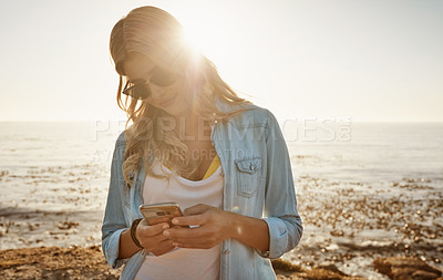 Buy stock photo Shot of a beautiful young woman using a mobile phone at the beach