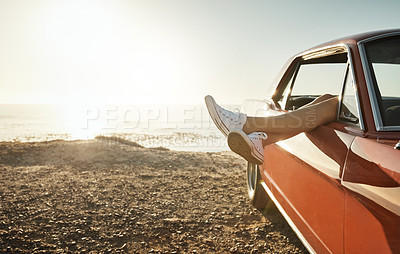 Buy stock photo Cropped shot of a woman's legs hanging out a car window while on a road trip