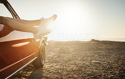 Buy stock photo Shot of an unrecognizable woman's legs sticking out the window of a car along the coast