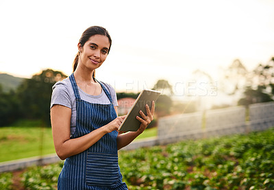 Buy stock photo Portrait of an attractive young woman using a tablet while working on her farm