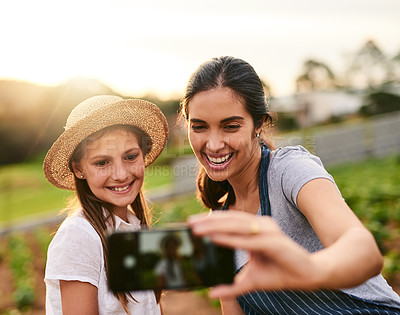 Buy stock photo Cropped shot of an attractive young woman and her daughter taking selfies while working on their family farm
