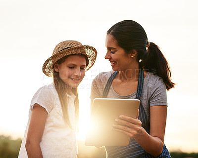 Buy stock photo Cropped shot of an attractive young woman using a tablet while working on the family farm with her daughter