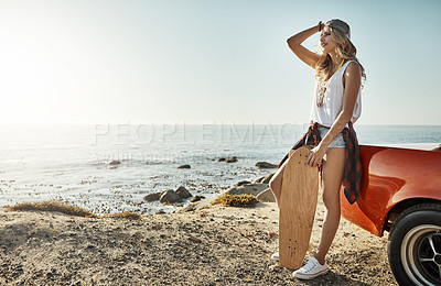 Buy stock photo Shot of an attractive young woman holding a skateboard while on a road trip