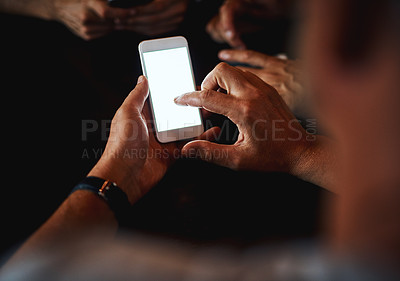 Buy stock photo Closeup of an unrecognizable man texting on his phone while being seated inside of a bar at night