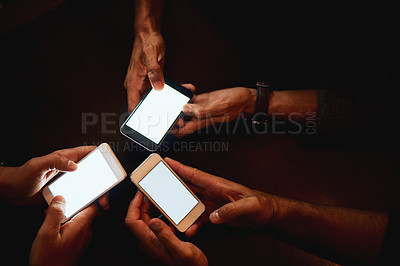 Buy stock photo Closeup of a group of unrecognizable people texting on their phones while being seated inside of a bar at night