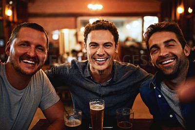 Buy stock photo Portrait of a cheerful young group of friends having beers together while being seated at a table inside a bar at night