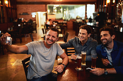 Buy stock photo Shot of a group of cheerful young friends taking a self portrait together while enjoying beer together at a bar during the night