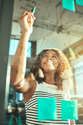 Buy stock photo Shot of a focussed young businesswoman putting up sticky notes on a glass wall while brainstorming in the office at work