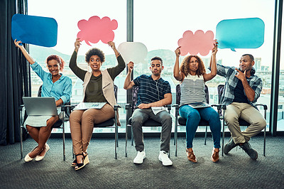 Buy stock photo Portrait of a cheerful young group of work colleagues seated next to each other while holding up signs inside of the office during the day
