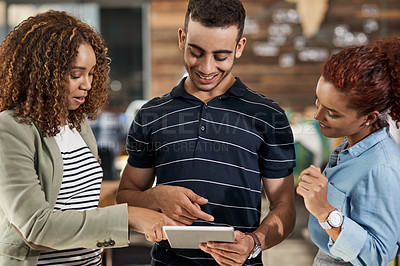 Buy stock photo Shot of a group of young designers working together on a digital tablet in an office