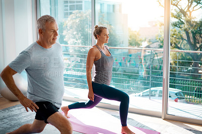 Buy stock photo Cropped shot of a mature couple stretching on yoga mats before working out at home