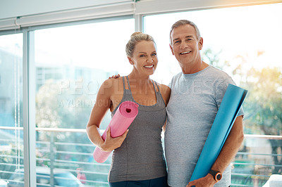 Buy stock photo Cropped portrait of an affectionate mature couple standing with their yoga mats at home