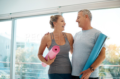 Buy stock photo Cropped shot of an affectionate mature couple standing with their yoga mats at home