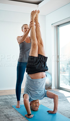 Buy stock photo Full length shot of a handsome mature man doing handstands with the help of his wife