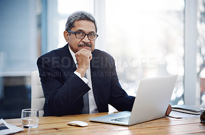 Buy stock photo Portrait of a mature businessman working on a laptop in an office