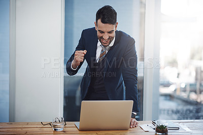 Buy stock photo Shot of a young businessman celebrating while working on a laptop in an office
