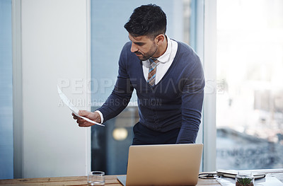 Buy stock photo Shot of a young businessman working on a laptop in an office