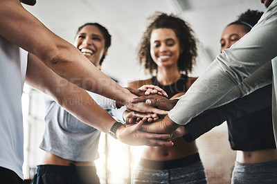 Buy stock photo Shot of a group of young people joining their hands together in solidarity at a gym