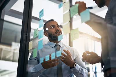 Buy stock photo Cropped shot of a group of two businessmen having a brainstorming session in a modern office
