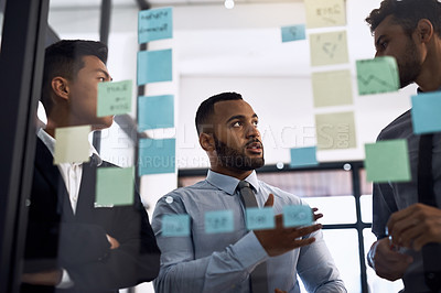 Buy stock photo Cropped shot of three businessmen having a brainstorming session in a modern office