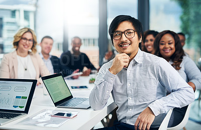 Buy stock photo Portrait of a young businessman having a meeting with his colleagues in a modern office