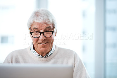 Buy stock photo Cropped shot of a handsome senior businessman working on his laptop at home