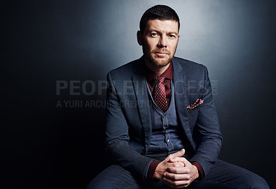 Buy stock photo Cropped portrait of a handsome young businessman sitting in the studio against a dark background
