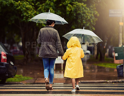 Buy stock photo Rearview shot of an unrecognizable little boy and his mother holding hands and walking in the rain outside