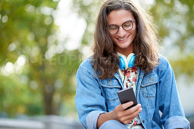 Buy stock photo Cropped shot of a handsome young male student using a cellphone on campus