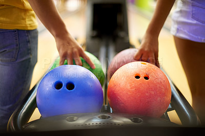 Buy stock photo Cropped shot of an unrecognizable couple grabbing a bowling ball in a bowling alley